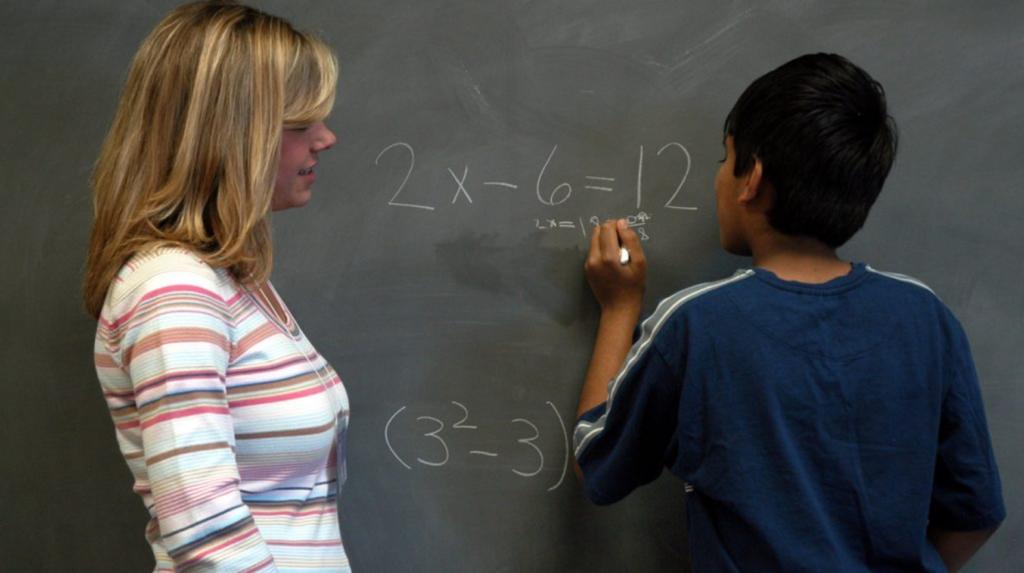 A student and a teacher doing a math problem at a chalkboard
